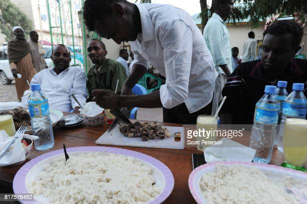 Somali restaurant worker cuts camel meat in preparation for an iftar fastbreaking meal during the Islamic holy month of Ramadan as the Horn of Africa...