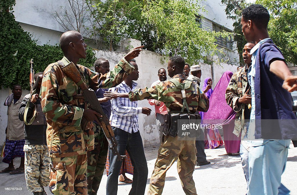 Somali security forces try to disperse Somali journalists outside a court in Mogadishu on February 5, 2013. A Somali court has sentenced a woman who said she was raped by security forces and journalist Abdiaziz Abdinuur, who interviewed her, saying they were guilty of insulting the state. Abdinuur, who works for several Somali radio stations as well as international media, was detained on January 10, 2013 after researching rampant sexual violence in Somalia. Human rights groups have condemned the ruling against the rape victim and Abdinuur. AFP PHOTO/Abdurashid Abdulle Abikar
