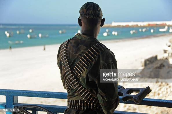 Somali soldier looks at the Lido beach from the terrace of the Lido seafood restaurant on January 22 2016 following an overnight attack on the...