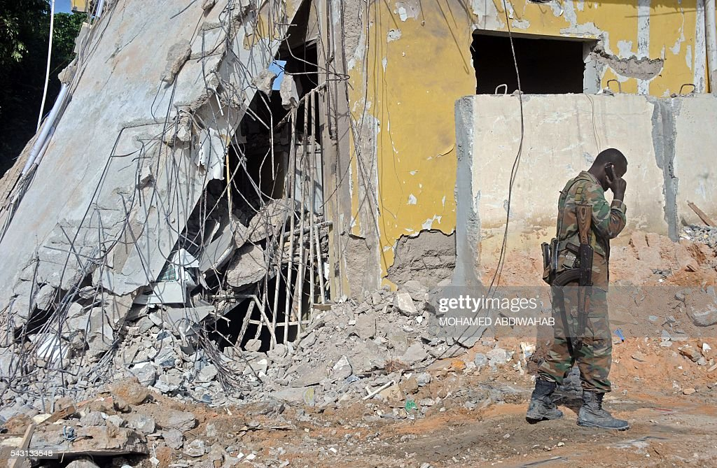 A Somali soldier speaks on the phone on June 26, 2016 by the scene of the terror attack on a hotel in the Somali capital Mogadishu that killed at least 11 people the day before and was swiftly claimed by Al-Qaeda-affiliated al-Shabab militants. The assault, the latest in a series by the Islamist group targeting hotels and restaurants, began when a suicide bomber detonated a car laden with explosives outside the building. Gunmen then stormed the Naasa Hablood hotel and gunfire rang out for several hours, witnesses said, before the authorities declared the attack over. / AFP / MOHAMED