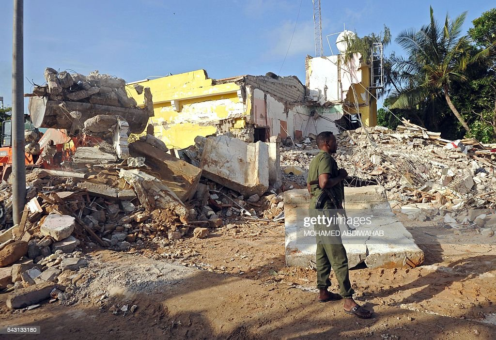 A Somali soldier stands guard on June 26, 2016 on the scene of the terror attack on a hotel in the Somali capital Mogadishu that killed at least 11 people the day before and was swiftly claimed by Al-Qaeda-affiliated al-Shabab militants. The assault, the latest in a series by the Islamist group targeting hotels and restaurants, began when a suicide bomber detonated a car laden with explosives outside the building. Gunmen then stormed the Naasa Hablood hotel and gunfire rang out for several hours, witnesses said, before the authorities declared the attack over. / AFP / MOHAMED