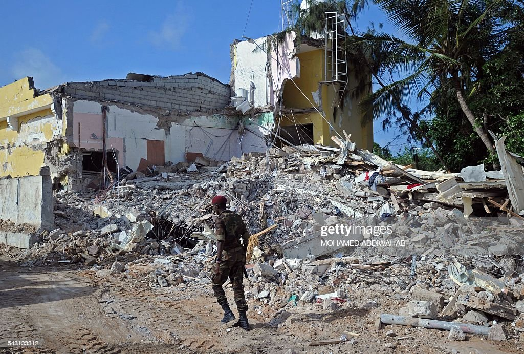 A Somali soldier walks on June 26, 2016 by the scene of the terror attack on a hotel in the Somali capital Mogadishu killing at least 11 people the day before and was swiftly claimed by Al-Qaeda-affiliated al-Shabab militants. The assault, the latest in a series by the Islamist group targeting hotels and restaurants, began when a suicide bomber detonated a car laden with explosives outside the building. Gunmen then stormed the Naasa Hablood hotel and gunfire rang out for several hours, witnesses said, before the authorities declared the attack over. / AFP / MOHAMED