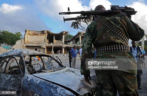 Somali soldiers and resident stand near wreckage car and buildings on February 27 in Mogadishu Somalia At least 14 people were killed on February 26...