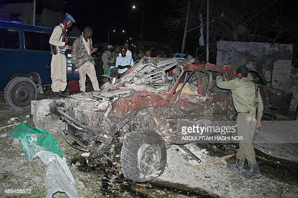 Somali soldiers look at the car bomb's wreck near a complex housing the office of Somalia's president and its prime minister in Mogadishu on...