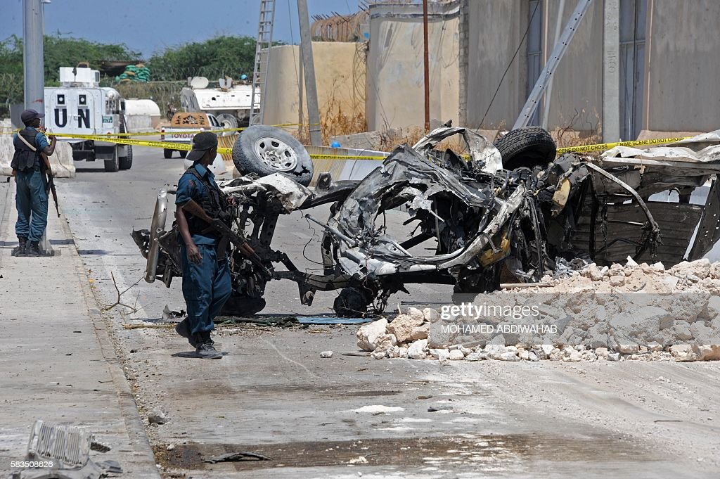 TOPSHOT Somali soldiers pass near the wreckage of a car bomb outside the UN's office in Mogadishu on July 26 2016 At least 13 people were killed on...