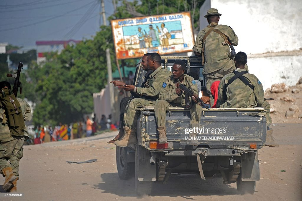Somali soldiers patrol in a pickup truck near the site where Al Shebab militants carried out a suicide attack against a military intelligence base in...