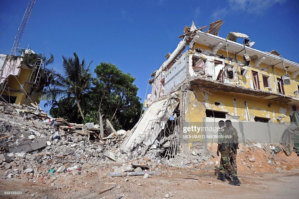 Somali soldiers stand guard on June 26, 2016 on the scene of the terror attack on a hotel in the Somali capital Mogadishu that killed at least 11 people the day before and was swiftly claimed by Al-Qaeda-affiliated al-Shabab militants. The assault, the latest in a series by the Islamist group targeting hotels and restaurants, began when a suicide bomber detonated a car laden with explosives outside the building. Gunmen then stormed the Naasa Hablood hotel and gunfire rang out for several hours, witnesses said, before the authorities declared the attack over. / AFP / MOHAMED