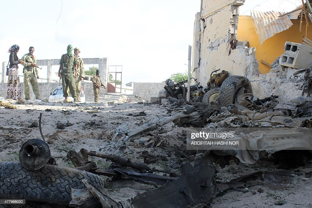 Somali soldiers stand next to the site where Al Shebab militants carried out a suicide attack against a military intelligence base in Mogadishu on...