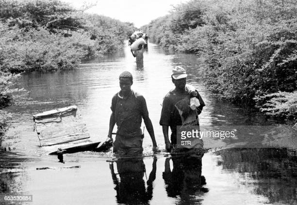 Somali villagers wade 02 December through deep flood waters which have filled what used to be a path leading to their village Torrential rains...