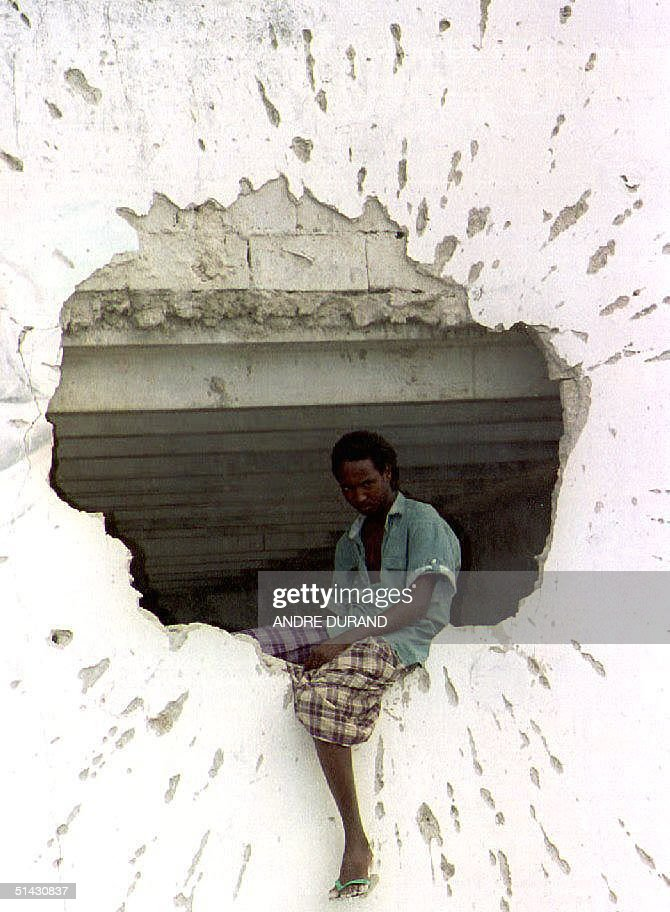 Somali watches the street 06 May 1993 from his perch on the edge of a hole blasted into the wall of a house by a rocket during fighting between...