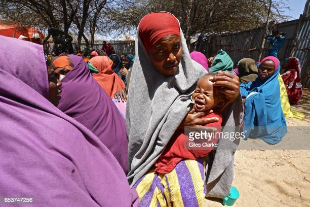 Somali woman and a baby wait for humanitarian aid registration at a World Food Program center in Mogadishu According to an United Nations February...