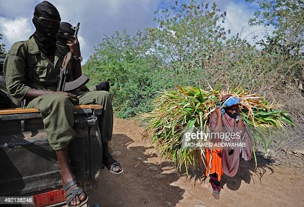 A Somali woman carrying goods walks past Somali soldiers patrolling on a road between Mogadishu and Jowhar some 90 kilometers north of the Somali...
