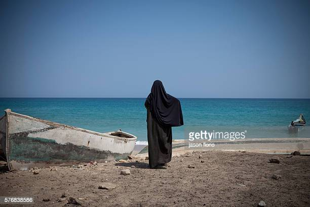 A Somali woman in a black Muslim hijab faces away from the camera toward to the Indian ocean at the village of Elayo SomaliaElayo was a renowned...