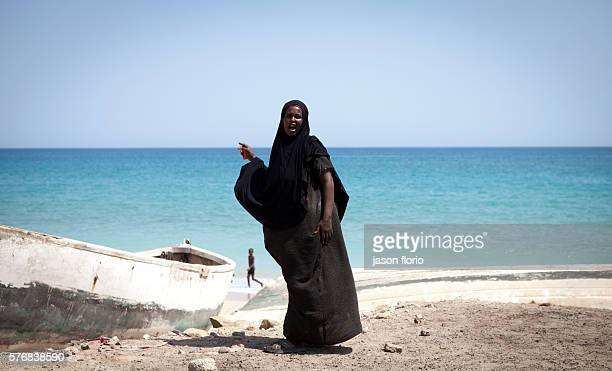 A Somali woman in a black Muslim hijab faces towards the camera with her back toward to the Indian ocean in the village of Elayo Somalia while a...