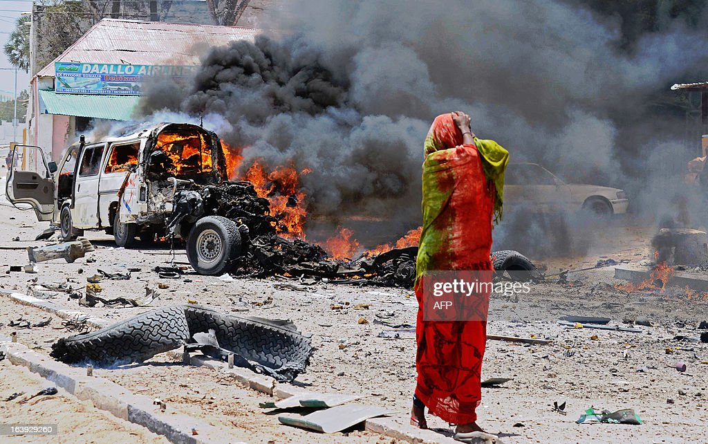 A Somali woman reacts on March 18, 2013 near the site of a car bomb in central Mogadishu. At least eight people were killed on March 18 by a car bomb in central Mogadishu in one of the bloodiest attacks in the war-ravaged capital in recent months, police said. AFP PHOTO/Mohamed Abdiwahab