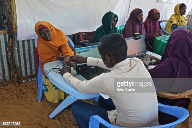 Somali woman with a World Food Program volunteer registering for humanitarian aid at a World Food Program center in Mogadishu Personal details and...