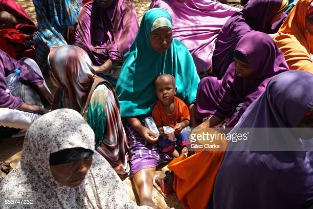 MOGADISHU SOMALIA MARCH 7 2017 Somali women and a baby wait for humanitarian aid registration at a World Food Program center in Mogadishu According...