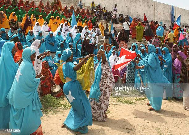 Somali women draped in their national flag dance at Konis stadium in Mogadishu during a ceremony marking the anniversary of Somalia's independence on...