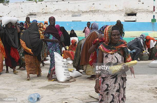 Somali women receive foodaid at a distribution station on July 15 2012 in the Howlwadaag district of Mogadishu Sweden's International Aid Services...