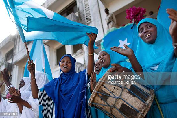 Somali women sing and wave the national flag during a ceremony marking President Sheikh Sharif Sheikh Ahem's first year in office at the Villa...