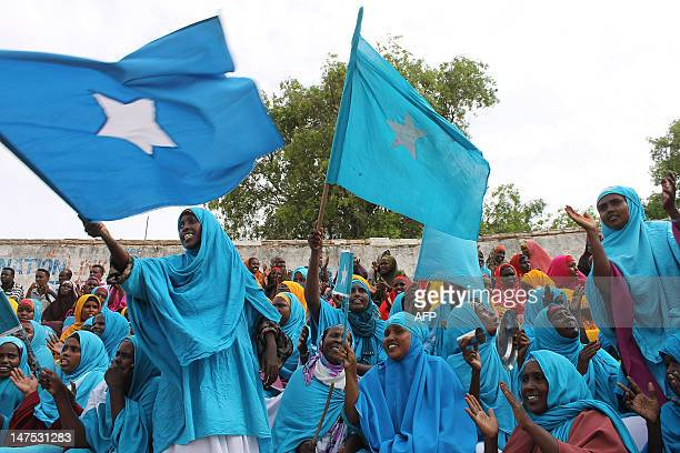 Somali women wave their national flag at Konis stadium in Mogadishu during a ceremony marking the anniversary of Somalia's independence on July 1...
