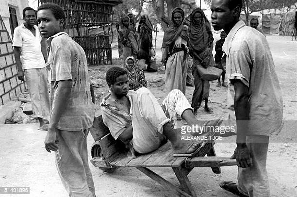 Somalia A wounded civilan is taken to a hospital after he had been shot during fighting 14 May 1992 between the forces of General Mohamed Farah Aidid...