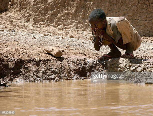 Somalia boy drinks water at a manmade dam in Bur Dhuxunle village in southern Somalia 370kms west of the capital Mogadishu 29 March 2006 as locals...