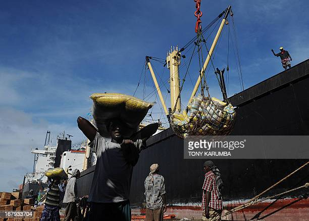 A Somalian porter carries a sack of imported noodles on his head on April 24 2013 in the sea port in Mogadishu from a foreign vessel like many of...
