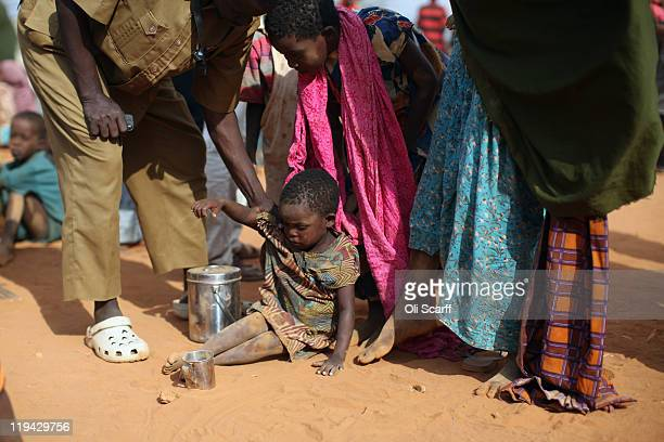 Somalian refugee child is helped up in the registration area of the Ifo refugee camp which makes up part of the giant Dadaab refugee settlement on...