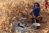 Somalian refugee cooks outside her home on the edge of the Ifo refugee camp which makes up part of the giant Dadaab refugee settlement on July 22...