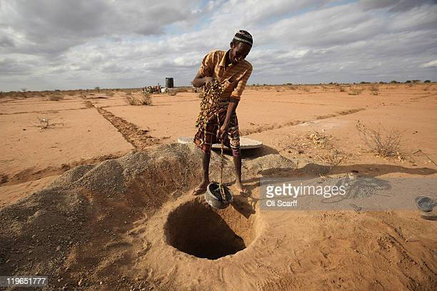 Somalian refugee helps to dig a latrine on the outskirts of the IFO refugee camp which makes up part of the giant Dadaab refugee settlement on July...