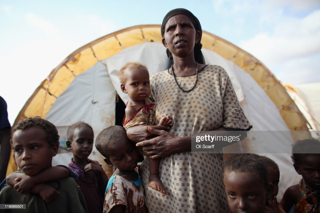 Somalian refugee holds her malnourished child outside her home on the edge of the Ifo refugee camp which makes up part of the giant Dadaab refugee...