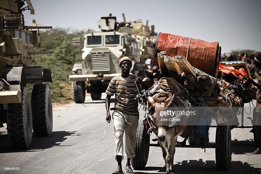 Somalian refugees from the al Shabaabcontrolled town of Afgooye pass AMISOM vehicles along a road on February 20 2012 in Mogadishu Somalia As...