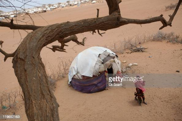 Somalian refugees leave their hut on the outskirts of the Dagahaley refugee camp which makes up part of the giant Dadaab refugee settlement on July...