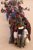 Somalian refugees queue for a bus to transport them from the IFO camp registration centre to the Dagahaley refugee camp which makes up part of the...