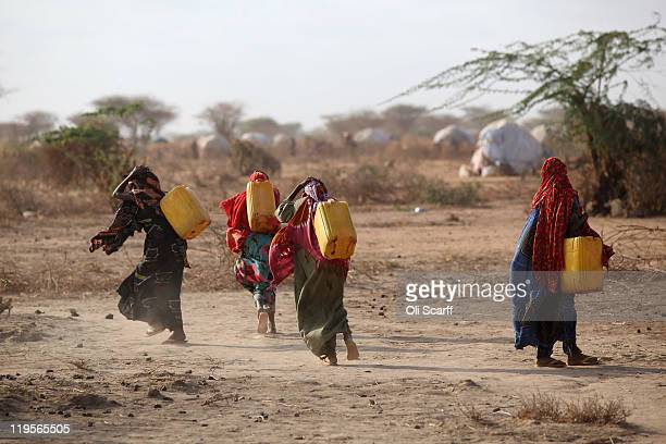 Somalian refugees return from collecting water at the edge of the Ifo refugee camp which makes up part of the giant Dadaab refugee settlement on July...