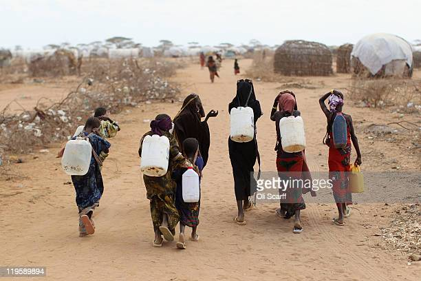 Somalian refugees return from collecting water at the edge of the Dagahaley refugee camp which makes up part of the giant Dadaab refugee settlement...