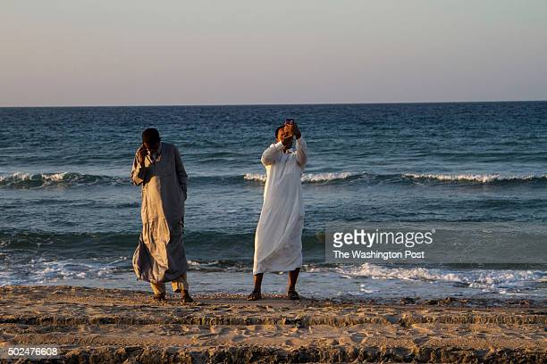 Somalilanders talk on the phone and take selfies along the coast of the Gulf of Aden near the main port of Berbera that they hope will one day...