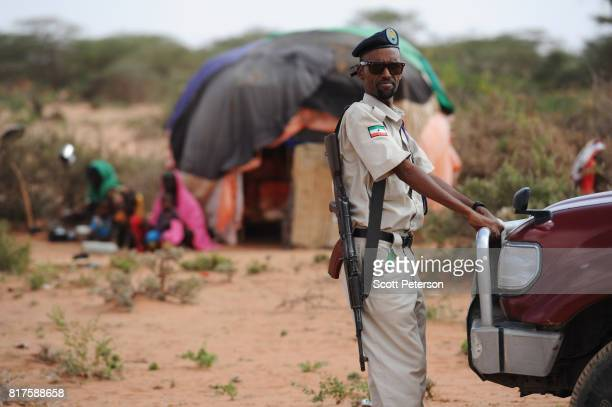 Somaliland policeman looks on as Somali families displaced by severe drought gather at a makeshift camp as the Horn of Africa faces severe drought on...
