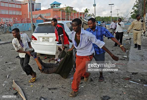 Somalis carry a body after an explosion on November 1 2015 near the damaged Sahafi hotel in Mogadishu At least 12 people were killed in the Somali...