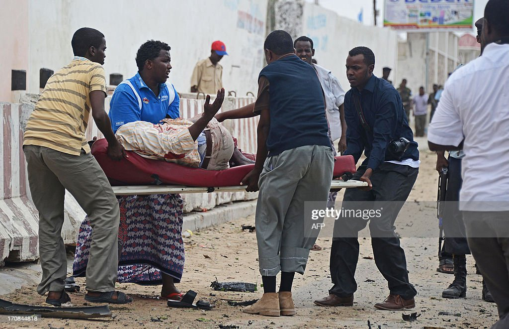 Somalis carry on June 19, 2013 an injured person after Al-Qaeda linked Shebab insurgents shot and blasted their way into the United Nations (UN) compound in Mogadishu. Three foreigners and at least two Somali security guards were killed during the attack -- the most serious attack on the UN in the troubled country in recent years.