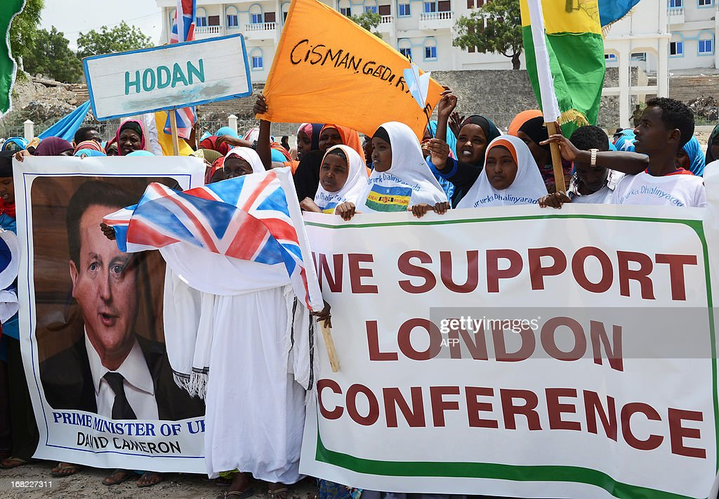 Somali's hold a banner with an image of Britain's Prime Minister David Cameron in Mogadishu, on May 7, 2013. Hundreds of Somalis marched through the capital to support a London conference attended by more than 50 countries and organisations, co-hosted by Britain's Prime Minister David Cameron and Somali President Hassan Sheikh Mohamud. The conference is a diplomatic meeting by leaders and organisations to co-ordinate efforts to help Somalia rebuild, following two decades of civil war. AFP PHOTO/Mohamed Abdiwahab