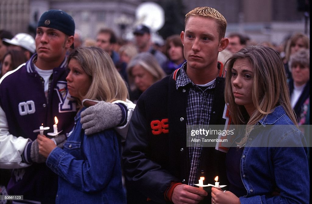 Somber Columbine High School student athletes hugging their girlfriends during candleight vigil for 12 students 1 teacher killed in suicide shooting...