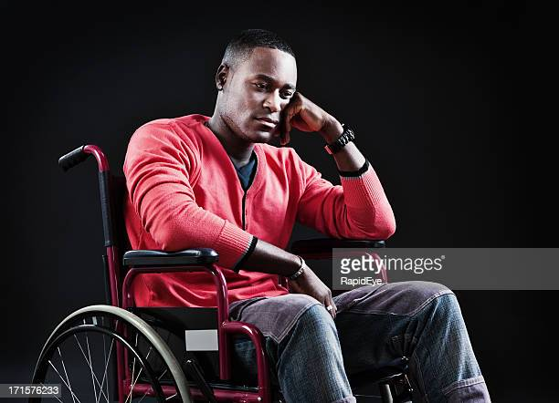 Somber young man sitting in wheelchair looks depressed