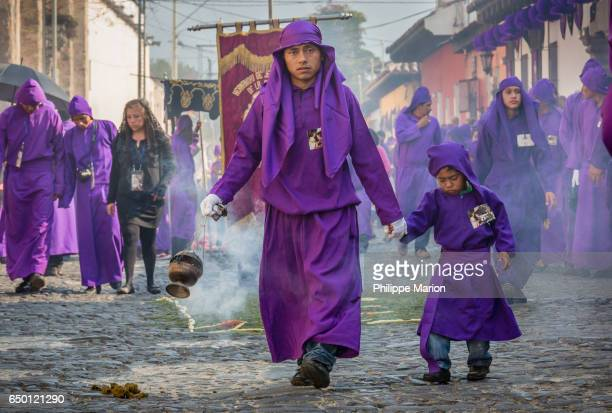 Sombre father and son in traditional clothing burning incense during Holy Week in Antigua, Guatemala