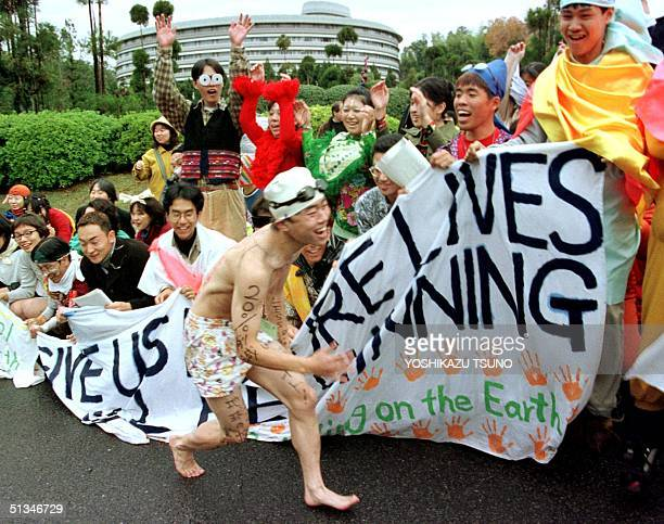 Some 100 Japanese youth holding banners do the wave as they protest against global warming as delegates to the UN conference on the climate change...