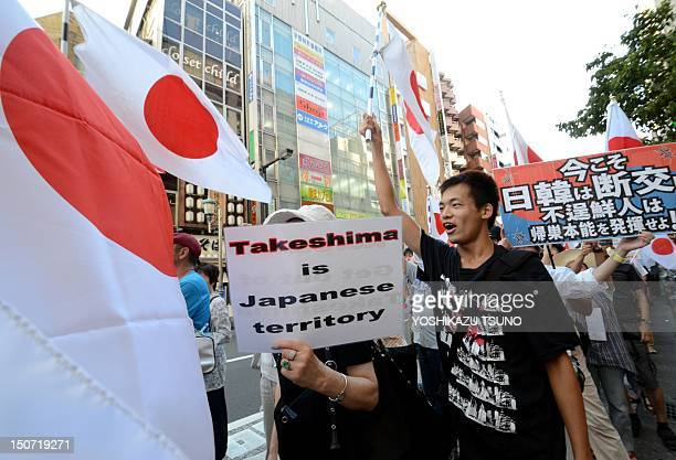 Some 200 Japanese nationalists carry Japan's national flags and placards to stage a demonstration against a visit by South Korean President Lee...