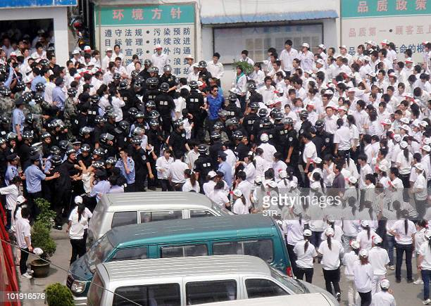 Some 2000 workers clash with police as they stage a strike outside the Taiwanfunded KOK Machinery rubber factory in Kunshan east China's Jiangsu...