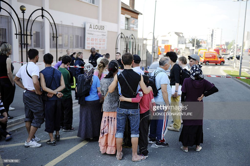 Some 250 people from the Roma community stands behind police barriers on April 25, 2013 in the Paris' suburb of Bobigny, after being evacuated as a large fire caught in a nearby factory spead in their camp.
