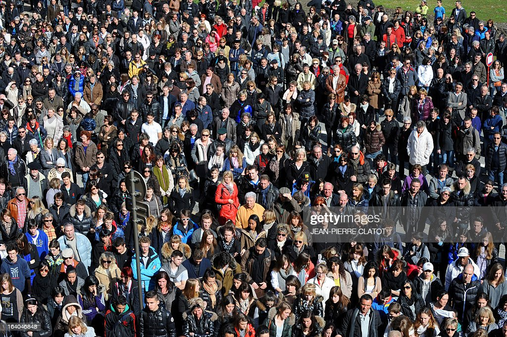 Some 3.500 people observe a minute of silence in front of the city hall during a silent marche on March 19, 2013 in Albertville, central France, in homage to jeweler Philippe Collier killed in his shop during a robbery on March 14. AFP PHOTO / Jean Pierre Clatot